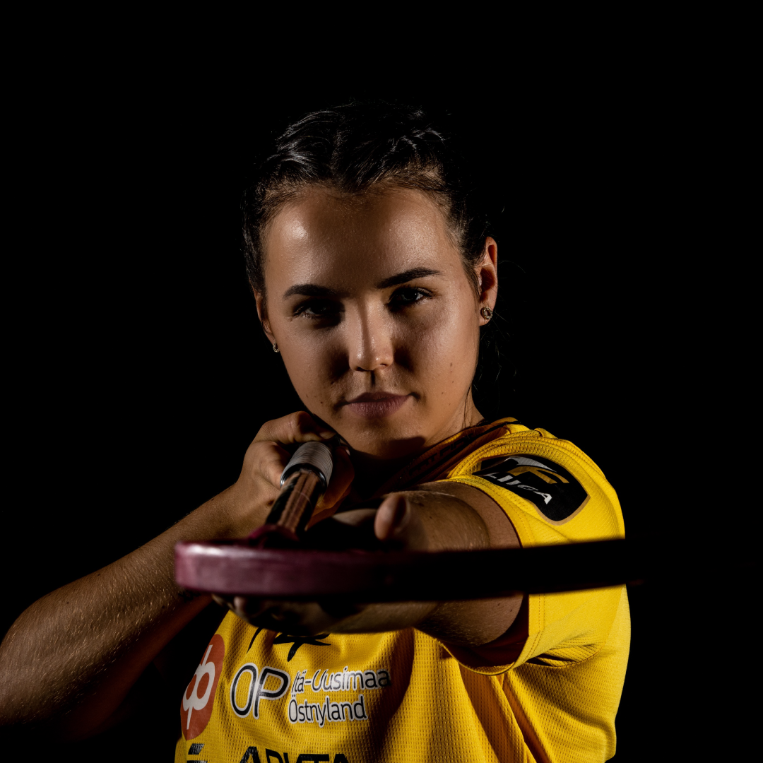 Fokusbild von Celine Stettler mit Unihockeystock Richtung Kamera gehalten mit schwarzem Hintergrund