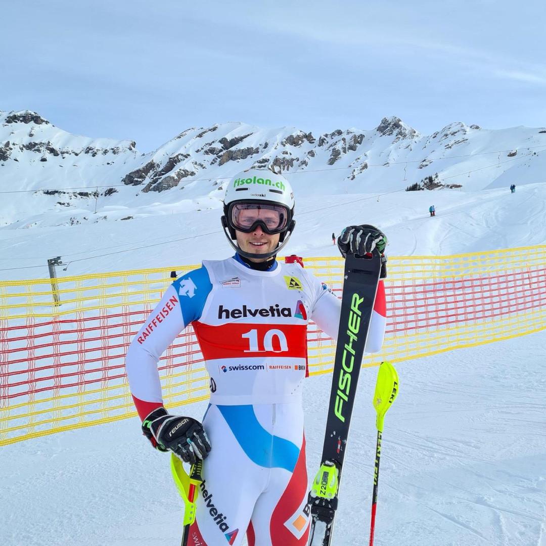 Noel von Grünigen mit Skiern in der Hand vor einem Bergmassiv